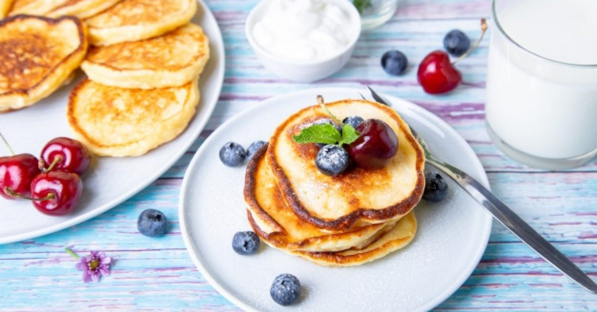 cottage-cheese-pancakes-syrniki-homemade-cheesecakes-from-cottage-cheese-with-sour-cream-berries-milk-traditional-russian-dish-close-up_165587-58