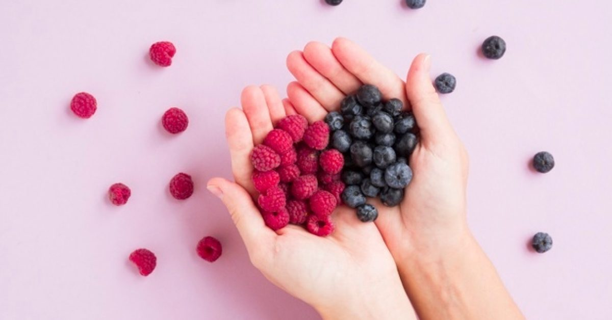 overhead-view-hands-holding-red-raspberries-blueberries-pink-background_23-2148103718