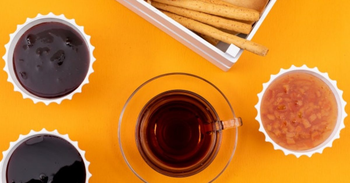 top-view-tea-with-jam-crackers-yellow-surface-horizontal_176474-860